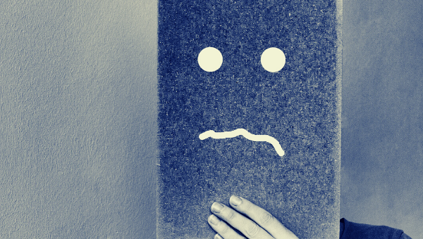 A photo of someone holding up a piece of cardboard over the face with a sad face spray painted on it.
