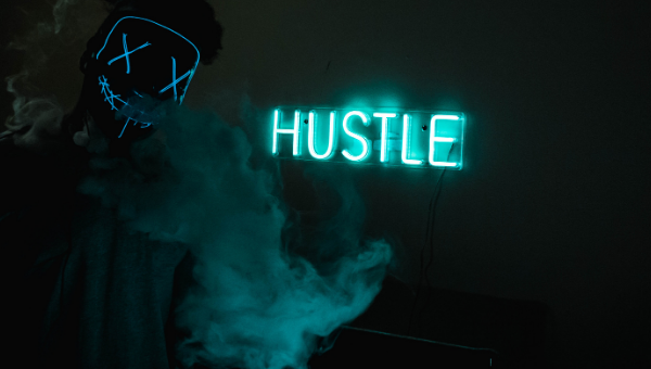 """A picture of a dark and mysterious background with a mint-green luminescent sign that says """"hustle"""" and a puff of luminescent green smoke/mist."""